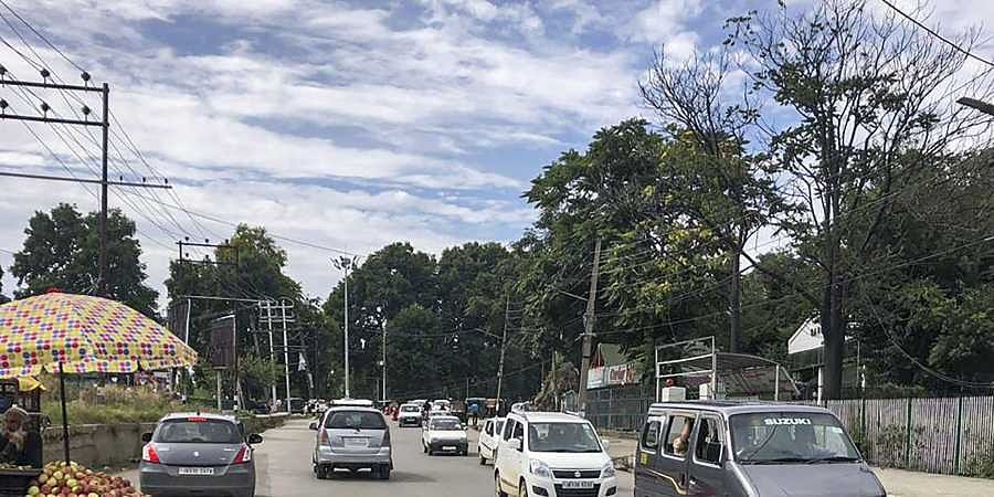 Private vehicles ply on a road after authorities eased restrictions in some parts of Srinagar on Saturday, August 17.