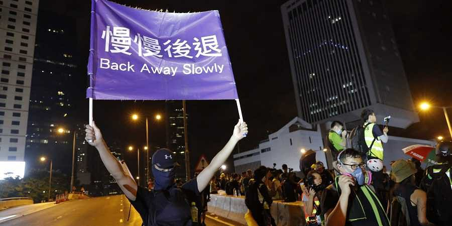 A demonstrator holds up a sign reading 'Back away slowly' to encourage other demonstrators to leave, near the Chinese Liaison Office in Hong Kong, Sunday, Aug. 18, 2019.