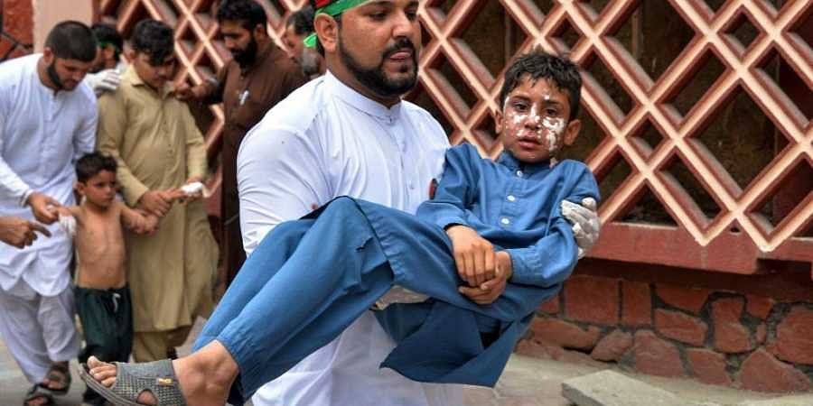 A volunteer carries an injured boy to a hospital, following multiples of bomb blasts in Jalalabad on August 19, 2019.