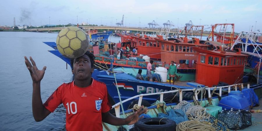 A football enthusiastic showing his skill after boarding on a fishing boat which all set to venture into the sea after 45 day trawling ban .A scene at Kalamukku harbour in Kochi