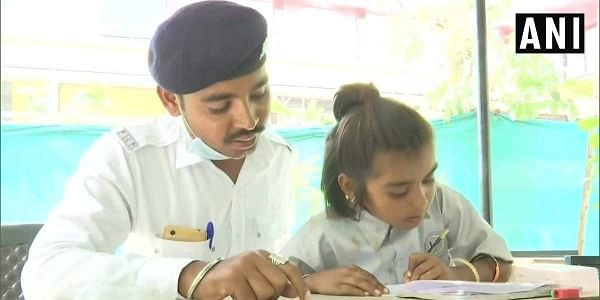 Ahmedabad City Traffic Police imparts free education to children residing on footpaths under their project called 'Police Pathshala'. Around 150-200 children are getting education in three centers across the city. (Photo | ANI Twitter)