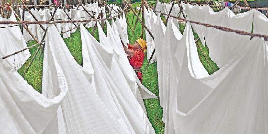 79-year-old Pratti, a member of the Vannan community, drying clothes at Dhobi Khana in Fort Kochi