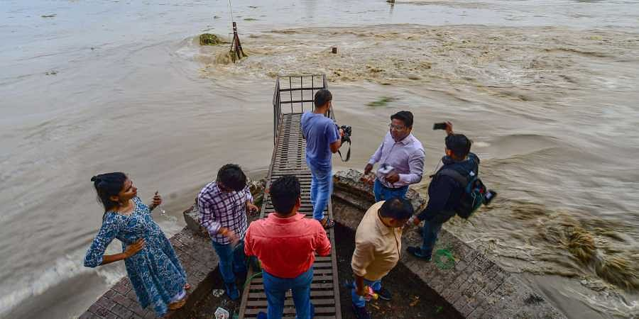 Media persons click pictures as the Yamuna river surges following the release of water from the Hathinikund Barrage in New Delhi Tuesday August 20 2019.