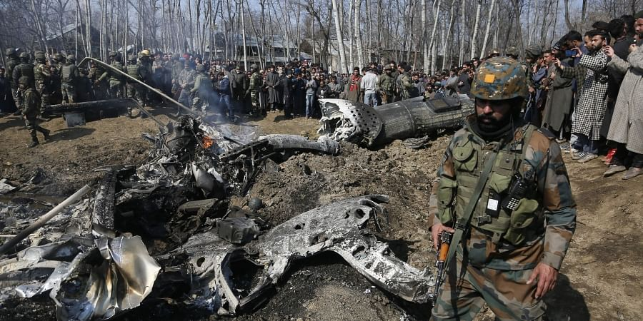 Indian army solider walks past the wreckage of an Indian aircraft after it crashed in Budgam area in the outskirts of Srinagar.