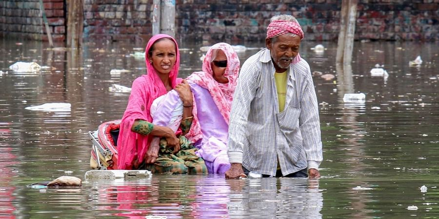 A rickshaw puller wades through a flooded road while carrying an elderly patient along with her relative to a hospital, in Bathinda.