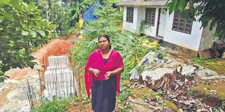 Soumya Shiju, stands in front of her house which was damaged after a massive landslide eroded the earth beneath the building at Adimali near Munnar.  Five of her family living at the foothill were killed as the debris fell atop their house