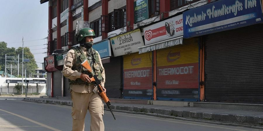 A security personnel patrols a street during restrictions in Srinagar Friday August 23 2019.