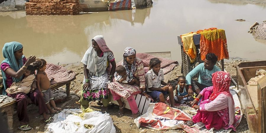 Flood affected families take shelter on a higher land as they wait for normalcy to return to their area near Sanour, in Patiala district.