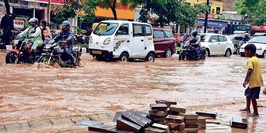 A child attempts to cross a waterlogged road at Ashok Nagar after a spell of heavy rain in Bhubaneswar on Friday.