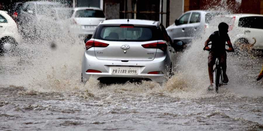 Vehicles wade through a waterlogged road after heavy rain in Patiala Sunday