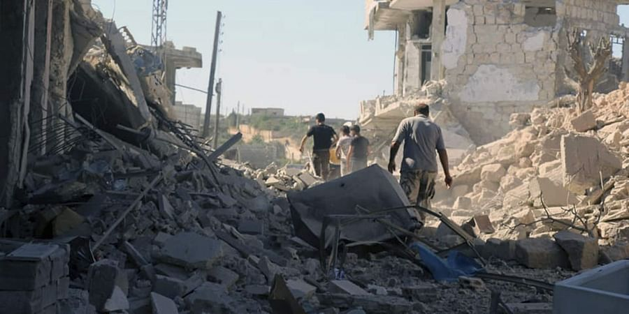 People inspecting destroyed buildings after airstrikes hit the town of Ihsem, in Idlib province, Syria.