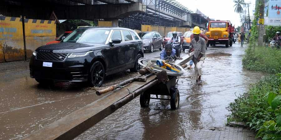 KSEB officials struggling to shift an electricity post through waterlogged Kundannoor Junction