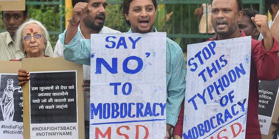 People raise slogans and hold placards as they protest against mob lynching and sexual violence against women in Ahmedabad. (Photo | PTI)