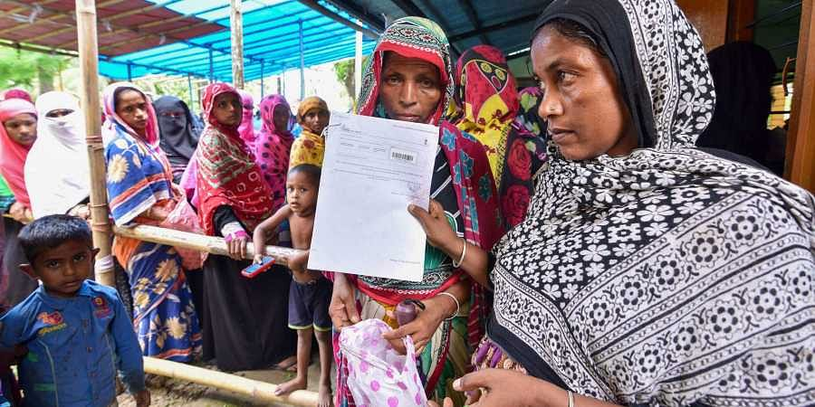 People check their names on the final draft of the state's National Register of Citizens after it was released, at a NRC Seva Kendra in Nagaon, Assam.