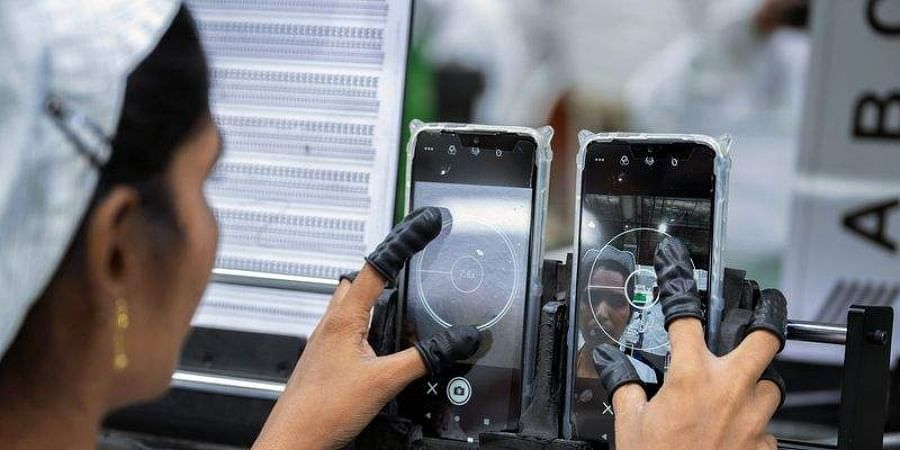 An employee tests the camera of a mobile phone.