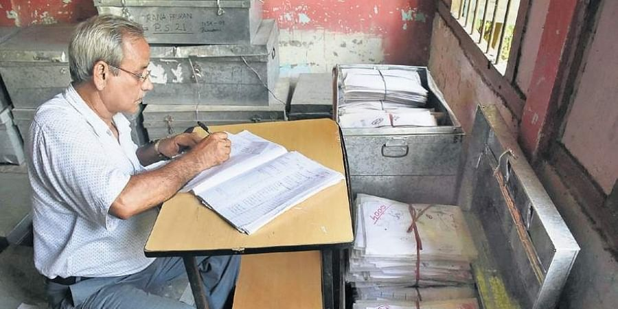 An official examines documents at an NRC Seva Kendra in Guwahati on Friday.