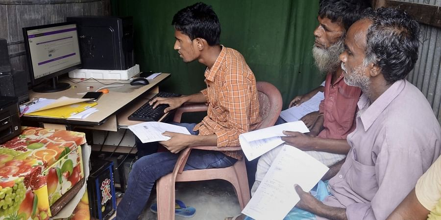 People check their names on the final NRC list.