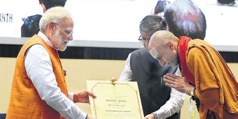 Prime Minister Narendra Modi confers Yoga Award to Bihar School of Yoga's Swami Niranjan in the national capital on Friday.