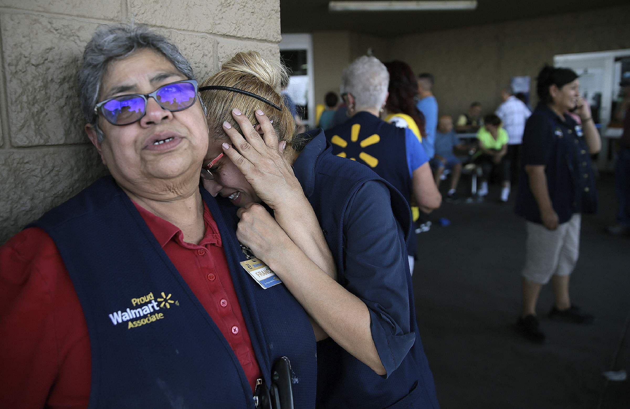 Walmart employees react after an active shooter opened fire at the store in Texas.