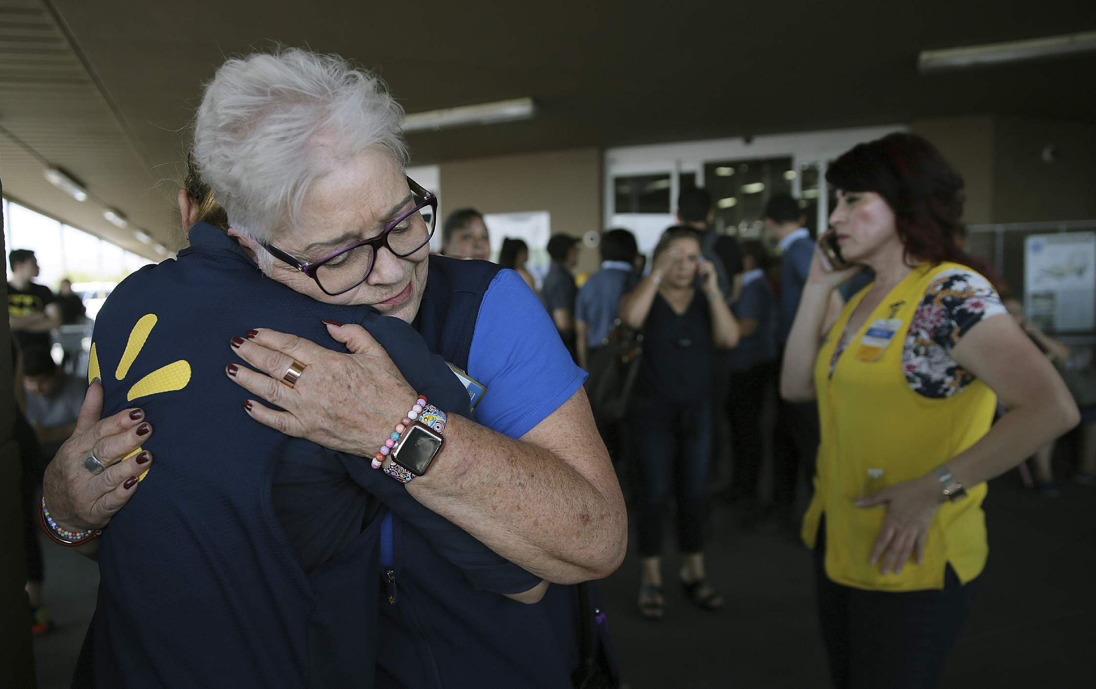 Walmart employees comfort one another after an active shooter opened fire at the store in Texas.