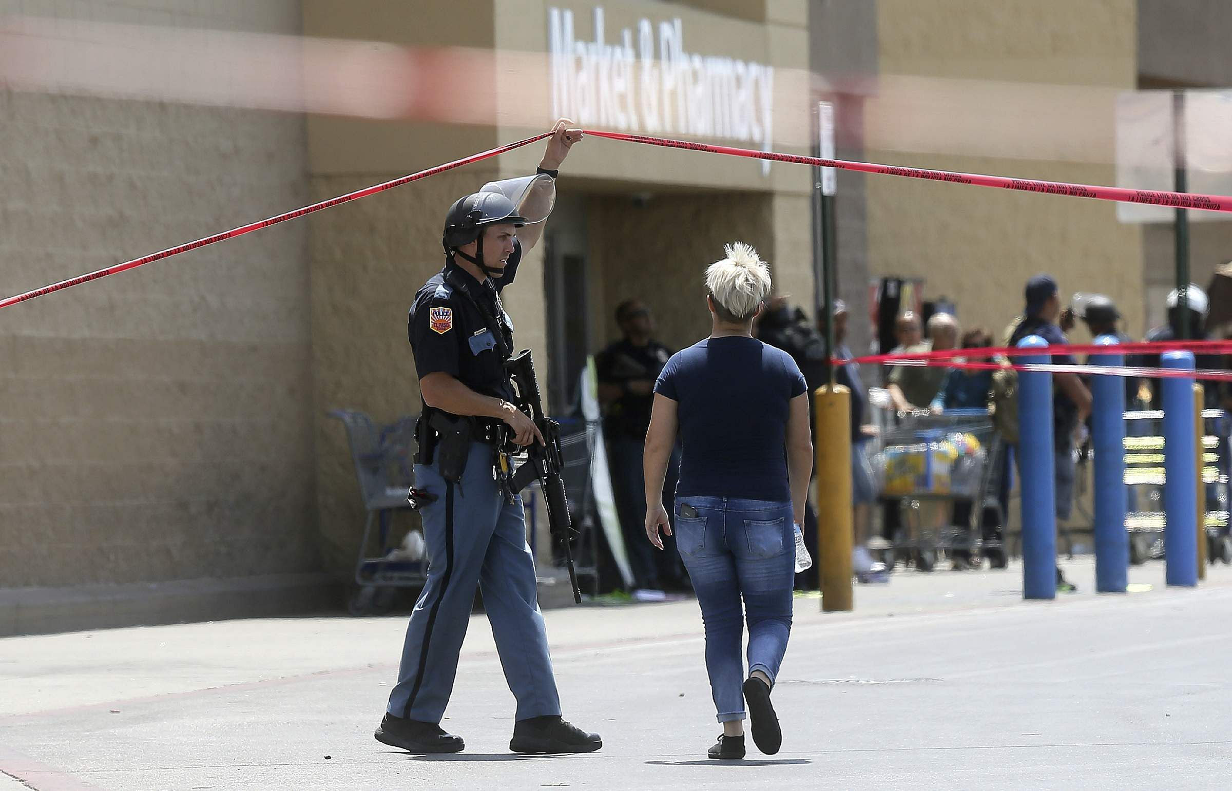 An employee crosses into the crime scene following a shooting at a Walmart in Texas.