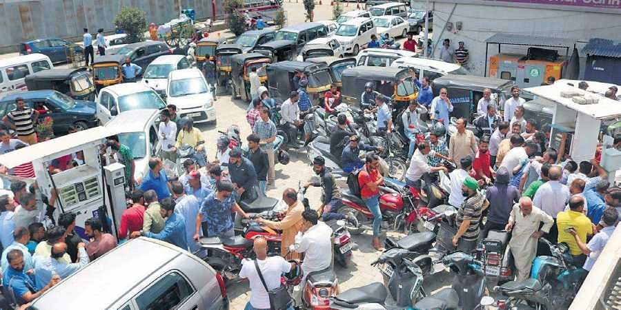 People wait to get petrol and diesel at a fuel pump in Srinagar on Saturday. There is a palpable tension among the locals after the Centre advised tourists to leave,  cut short Amarnath Yatra and boosted security deployment.