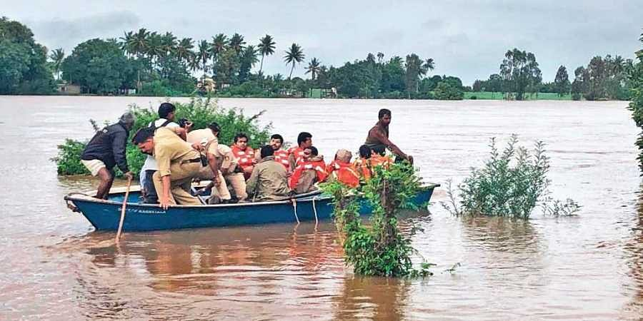 A group of villagers ferried to safer places on boats in Jamkhandi on Sunday