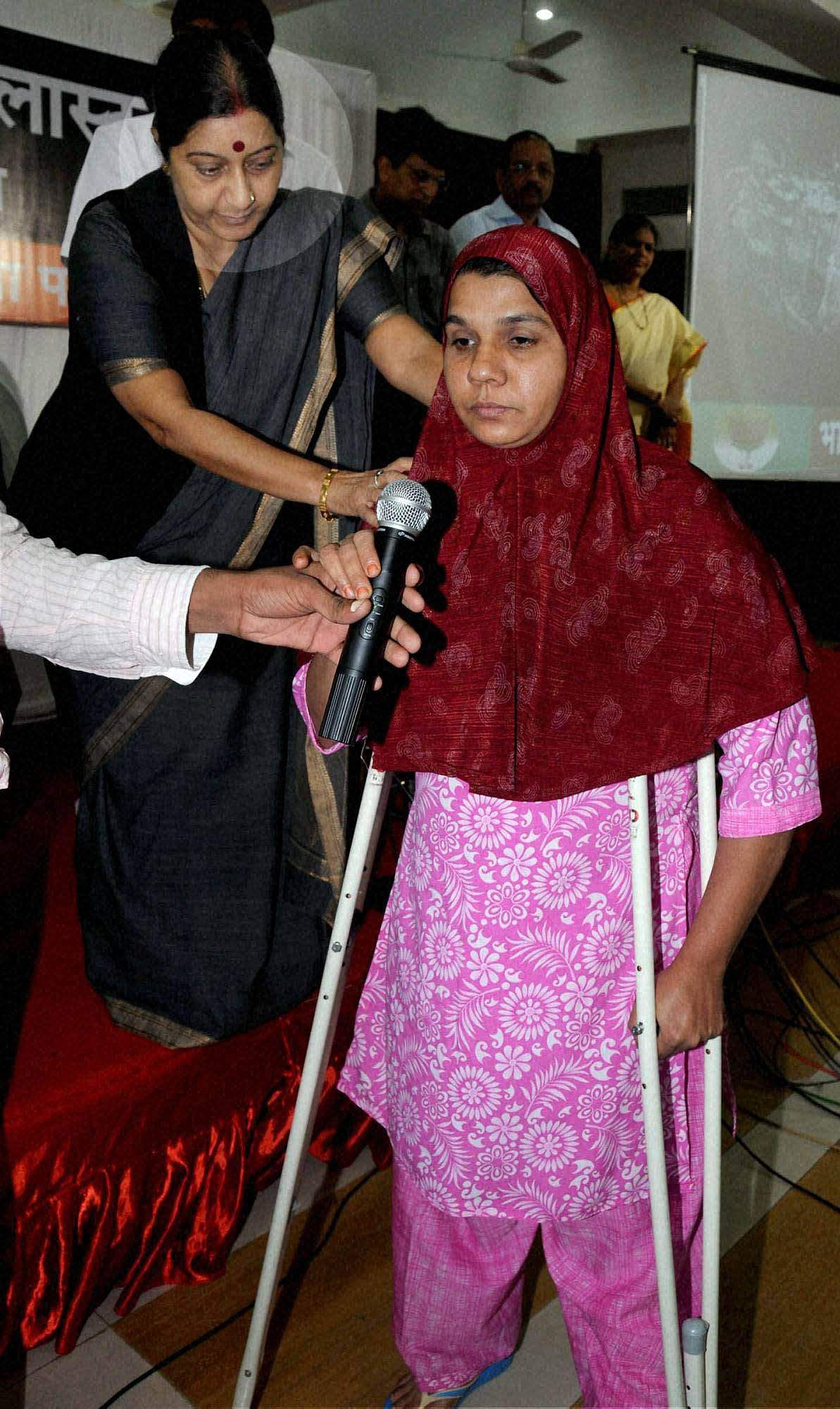BJP leader Sushma Swaraj helps a victim stand on her crutches during the 4th memorial day of 2006 bomb blast, in Mumbai.