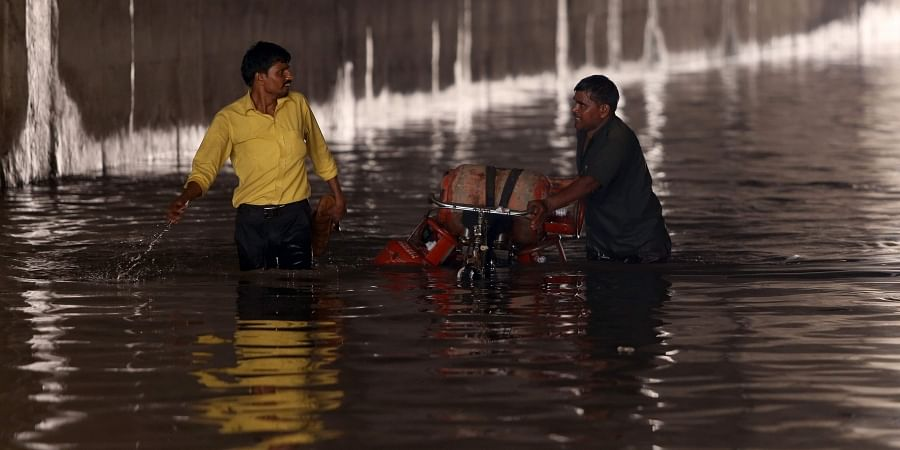 Vehicle wades through flooded underpass near Azad Market after heavy rainfall in New Delhi