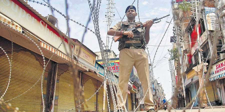 CRPF personnel stand guard during restrictions at Raghunath Bazar in Jammu on Monday. Kashmiri Pandits living there celebrated the Centre's decision