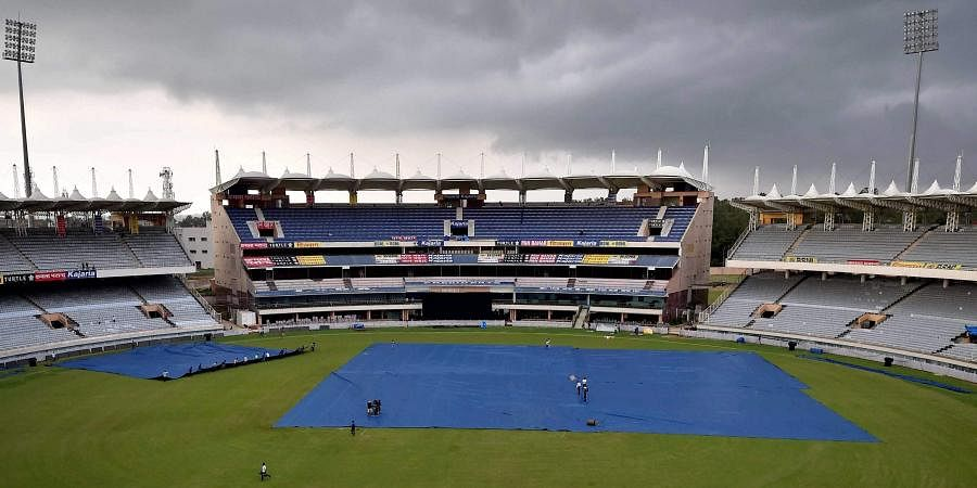 Groundsmen cover the pitch as dark clouds are seen in the sky over JSCA Stadium in Ranchi. (File| PTI)