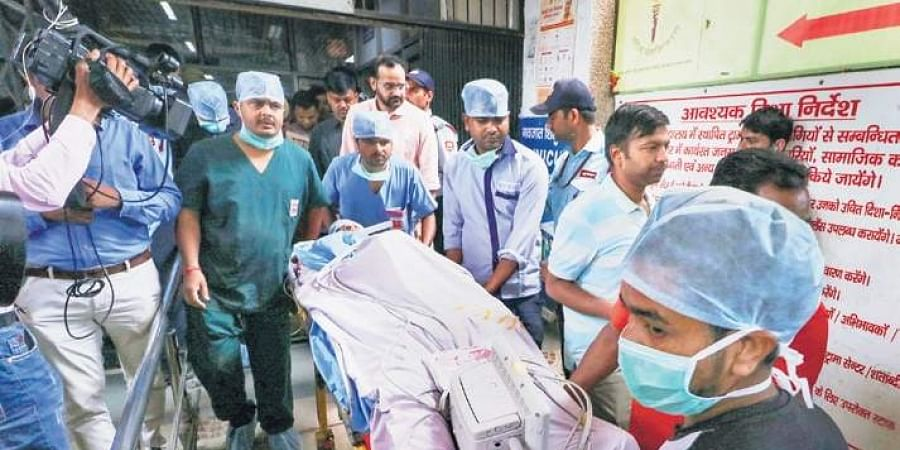 The lawyer of the Unnao rape survivor is wheeled by medical attendants outsidethe KGMC Trauma Centre in Lucknow for facilitating his airlift to New Delhi on Tuesday.