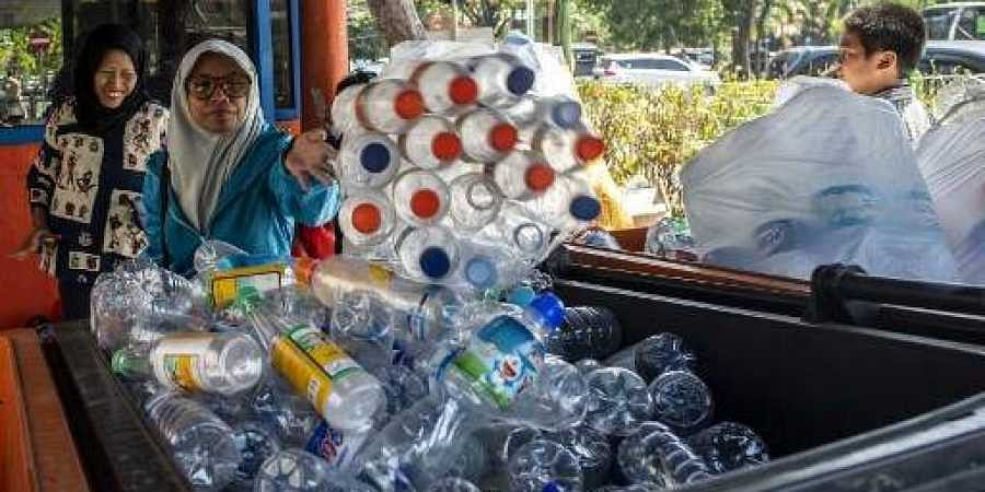 Commuters exchanging plastic bottles for Surabaya bus tickets at a terminal in the Indonesian city of Surabaya.