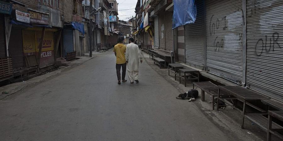 Kashmiri men walk past closed shops in central Srinagar, Tuesday, August 27, 2019.