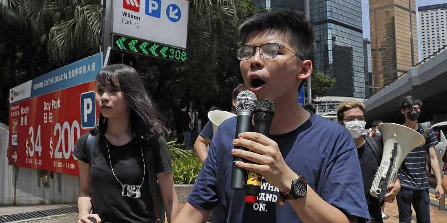 Pro-democracy activist Joshua Wong, center left, speaks as protesters surround the police headquarters in Hong Kong.