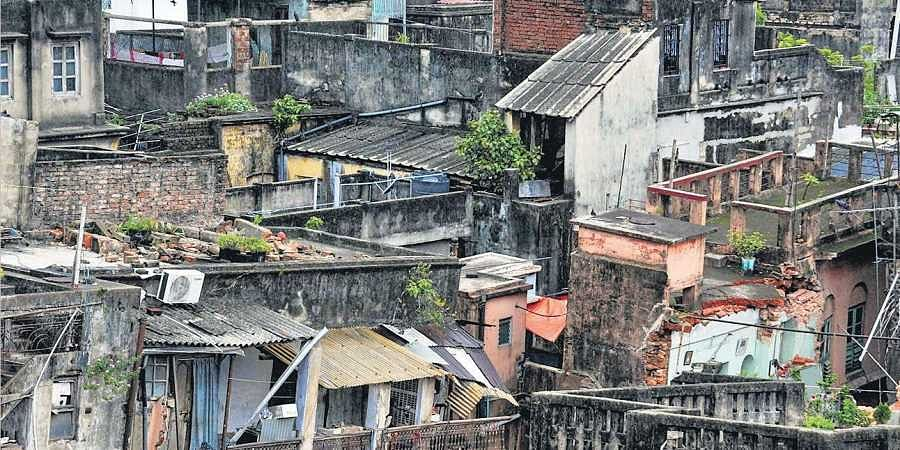 A view of the buildings in the Bowbazar area, where several houses have been damaged owing to tunneling for  East-West Metro corridor, in Kolkata on Thursday; (Below) Residents carrying out their belongings.