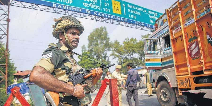 A BSF jawan stands guard as J&K Police personnel check vehicles on the Jammu-Srinagar highway in Kathua on Thursday. On the 39th day of the shutdown security forces continued to be deployed to maintain law and order.