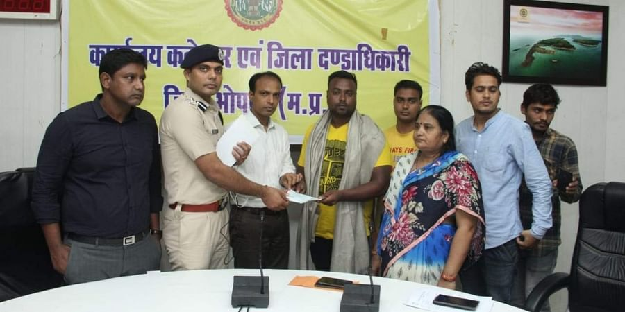 Brave heart swimmer being honoured by  district collector and SP in Bhopal on Saturday. | (Photo | EPS)