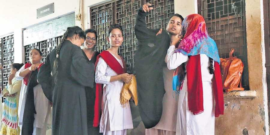 Students at the M G college in Uttar Pradesh's Firozabad change out of their burqas as they are not allowed to wear them in classrooms. While some colleges have changing rooms, others force them to change in the open