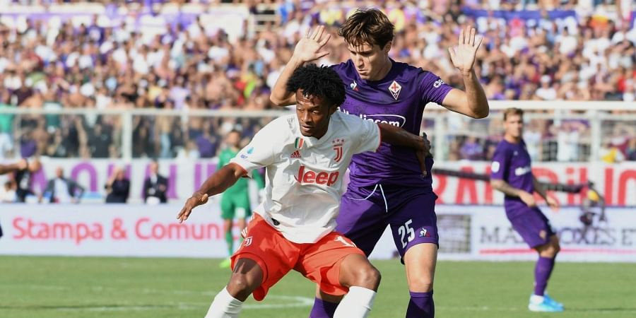Juventus Juan Cuadrado, left, holds back Fiorentina's Federico Chiesa during the Serie A soccer match between Fiorentina and Juventus, at the Artemio Franchi stadium in Florence, Italy, Saturday, Sept. 14, 2019. | AP