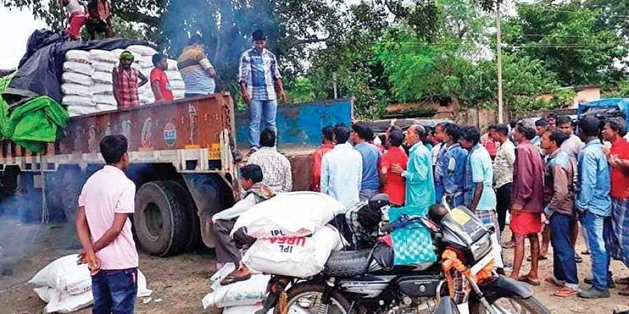 Farmers wait in queue near a truck to buy urea at Kalimela in Malkangiri district.