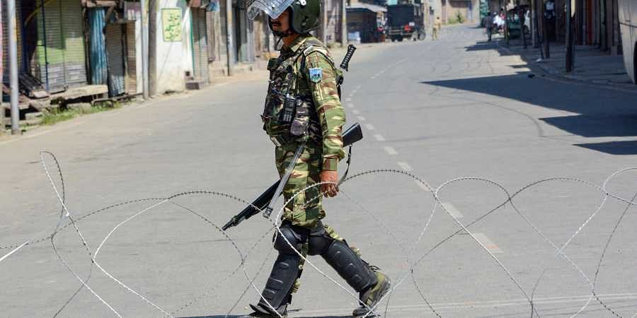 An Indian soldier patrols a curfewed street in Kashmir.