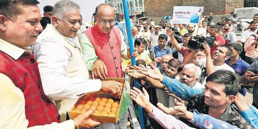 Union Minister VK Singh and BJP's Rajya Sabha member Vijay Goel share sweets with the people at Ajmeri Gate