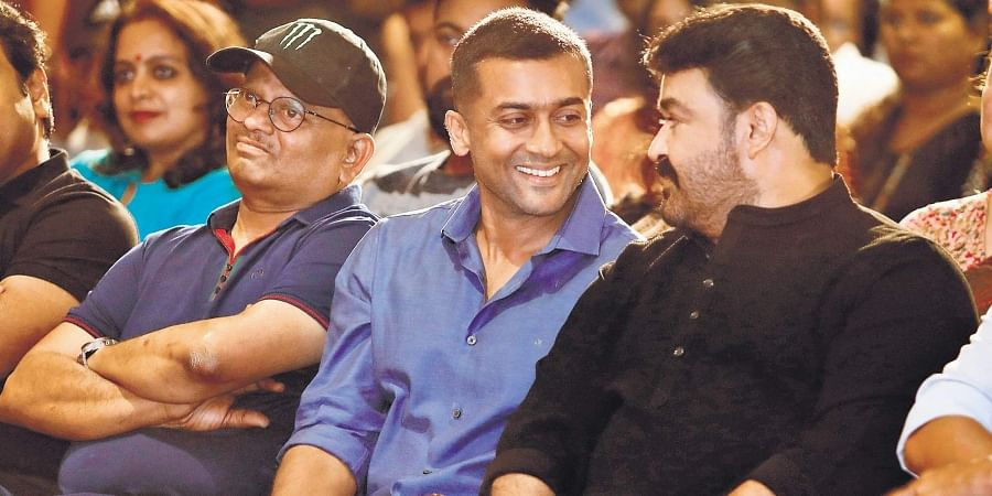 Mohanlal and Suriya sharing a light moment  at the promotions of Kaappaan  in Kochi on Tuesday. Director  K V Anand is also seen.