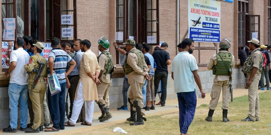 Security personnel stand guard as local people buy air-tickets from a special ticket counters set up by the government on the 29th day of restrictions after abrogration of the provisions of Article of 370 in Srinagar Monday September 2 2019. | PTI