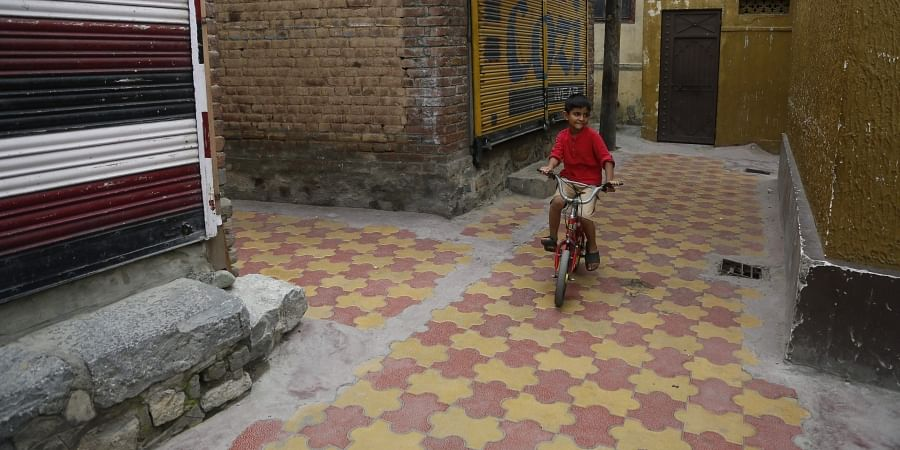 A Kashmiri child rides a cycle in a closed market area in Srinagar, Saturday, August 31, 2019. | AP