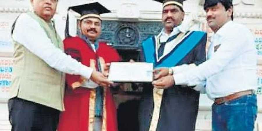 Mahadev (third from left) being presented with the doctorate.