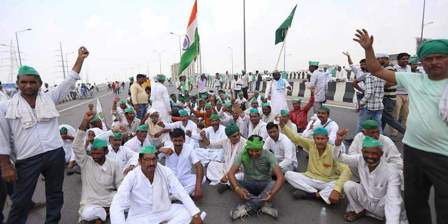 Hundreds of farmers walk towards Delhi at the UP-Delhi border during a protest march