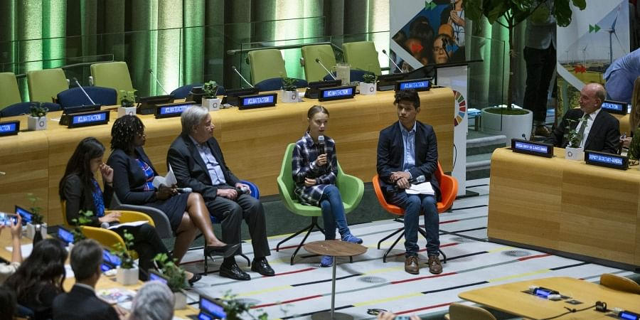 Swedish environmental activist Greta Thunberg, center, speaks to guests next to U.N. Secretary-General Antonio Guterres, center left, during the Youth Climate Summit at United Nations headquarters, Saturday, Sept. 21, 2019.