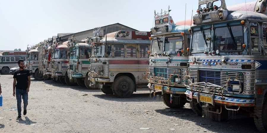 A man walks as passanger buses stand parked during restrictions after the abrogation of Article 370 and bifurcation of State in Srinagar Saturday September 14 2019. | PTI